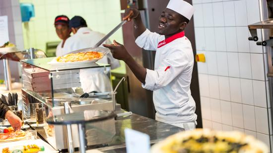 Collaborateur Sodexo entrain de servir une pizza